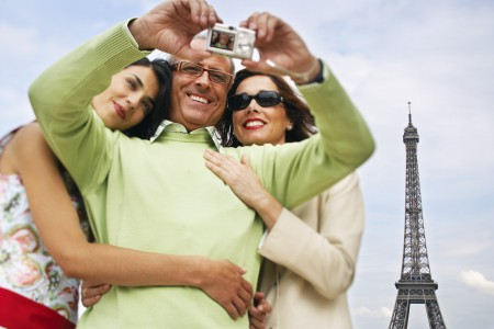 Family Using Digital Camera in Front of Eiffel Tower